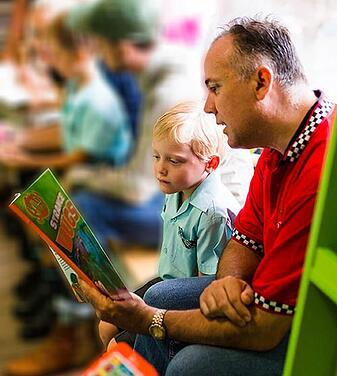 Dad reading to child in class